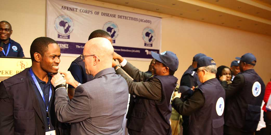 Dr Leo F. Weakland - Senior Adviser for Management and Operations at Africa CDC, and other dignitaries decorating FElTP graduates during the ACoDD launch 7 May 2018.