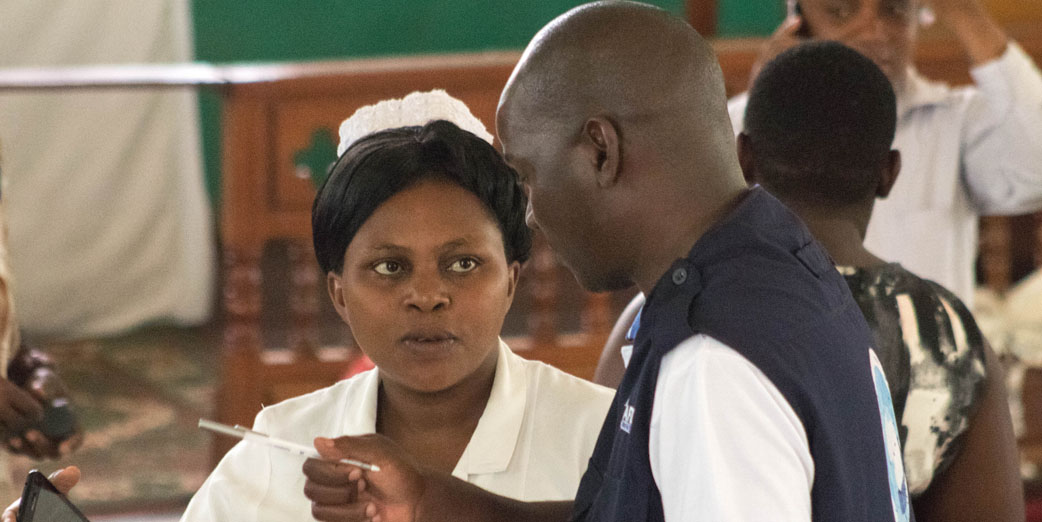 Dr Ben Masiira, Epidemiologist interviewing a nurse during a health workers sensitization activity during the Ebola outbreak in Kasese